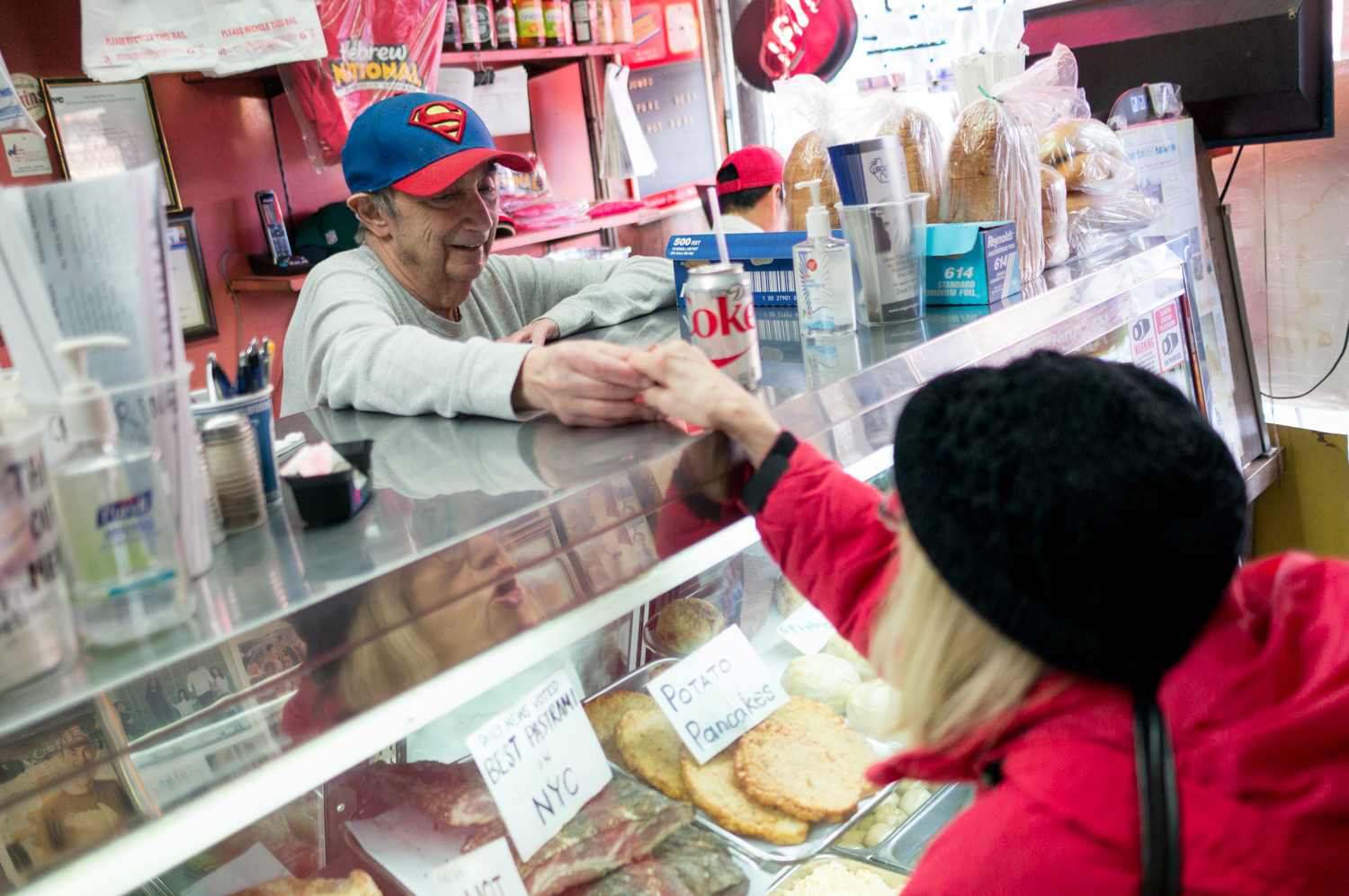 Fredy Loeser shakes a customer's hand at his well-established deli, located off bustling Broadway at 214 W. 231st St. Pamela Halpern, Loeser's daughter, has launched an online petition and has approached Community Board 8 to have a sign on the north side of West 231st honoring the deli.