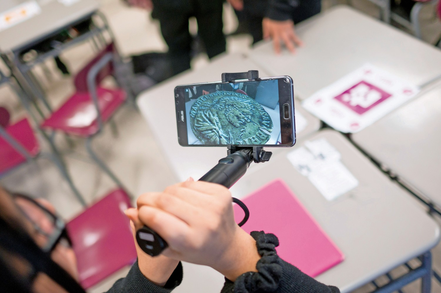 An InTech student looks at an augmented reality version of an ancient Roman coin through Google's app 'Expeditions AR.'