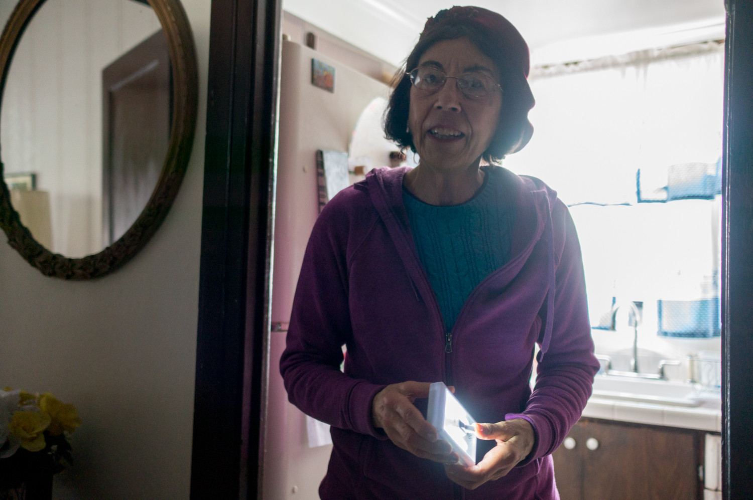 Eileen Fisher holds an LED light that she uses to see at night. After the winter storm knocked down a massive tree on Sylvan Avenue between West 256th and West 254th, Fisher and her husband have relied on their stove's burners for heat, while keeping milk outside in front of their house, nestled in the snow.