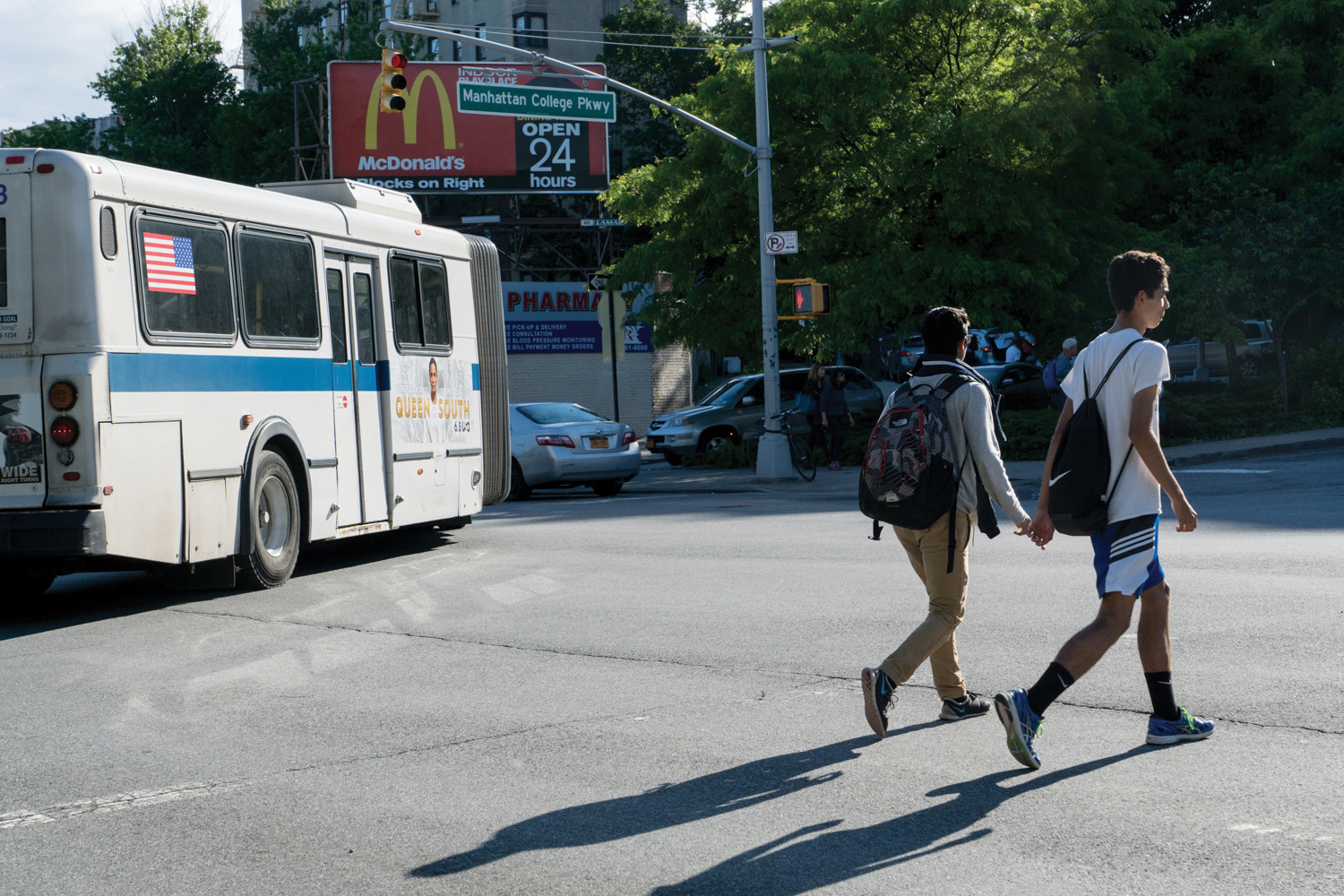 Pedestrians walk across Broadway while a bus makes a turn last year.