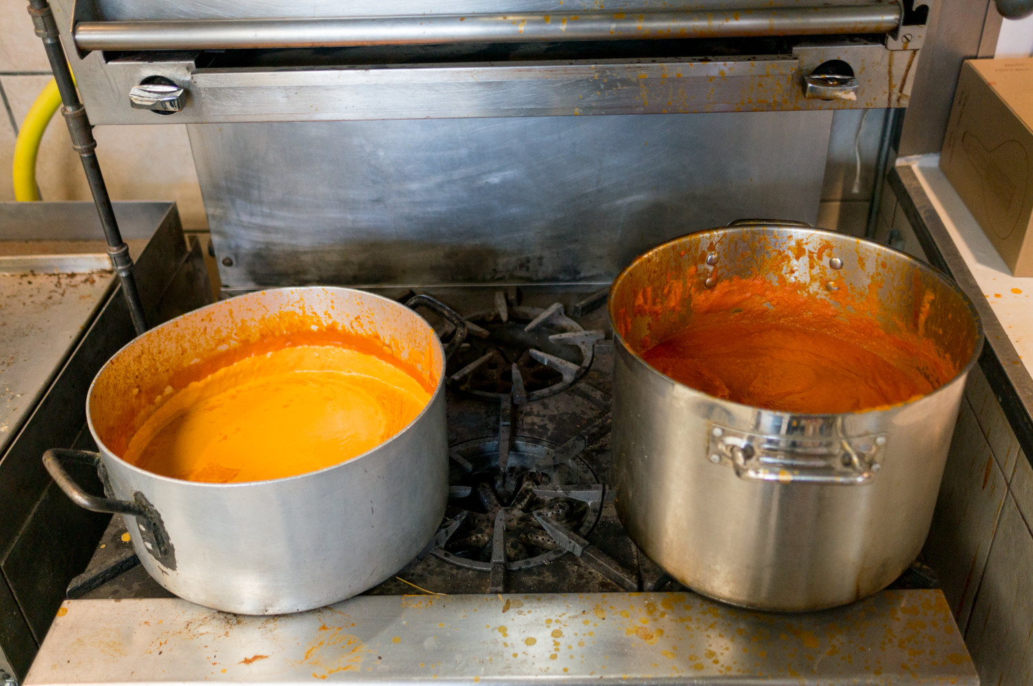Fresh pots of vodka sauce and tomato sauce sit on the stove in the kitchen of Caffe Buon Gusto near Manhattan, a restaurant that has two other locations in Manhattan and Brooklyn.