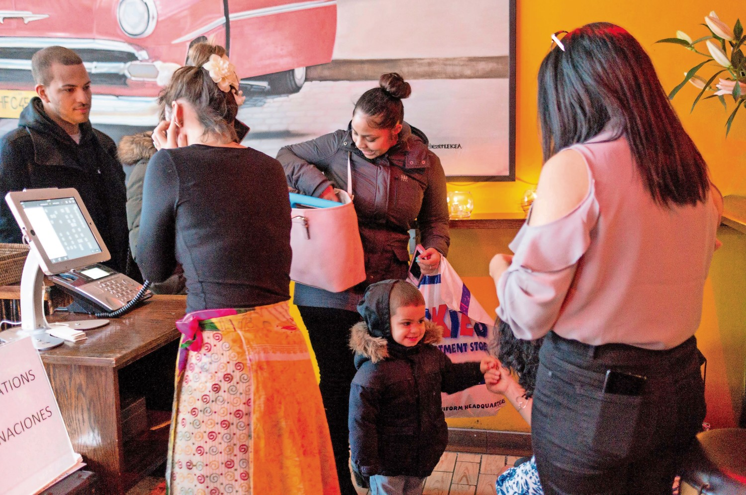 Lehman College student Christina Torres, center, arrives with her son Nathan Martinez at Amor Cubano, a Cuban restaurant in Harlem. Torres will be part of a weeklong trip to Cuba as part of her course work in Teresita Levy's class.