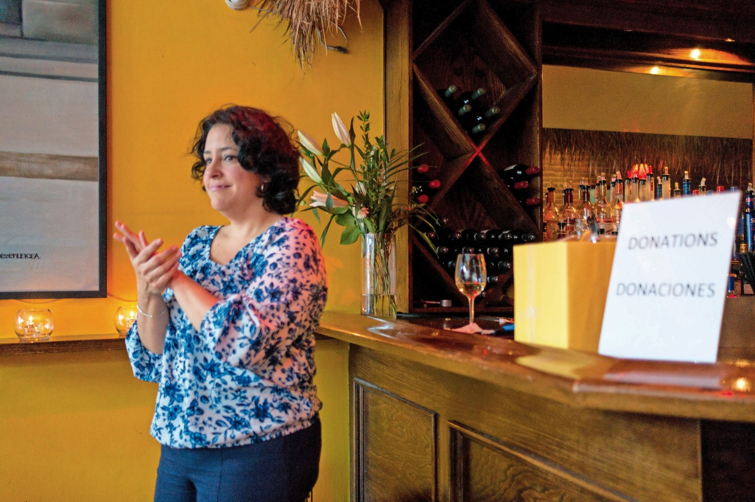 Teresita Levy, a professor of Latin American studies at Lehman College, claps along to the music of Trio La Cumbancha at Amor Cubano, a Cuban restaurant in Harlem. Levy held a fundraiser at the restaurant for a weeklong trip she and her students are planning as part of their coursework.