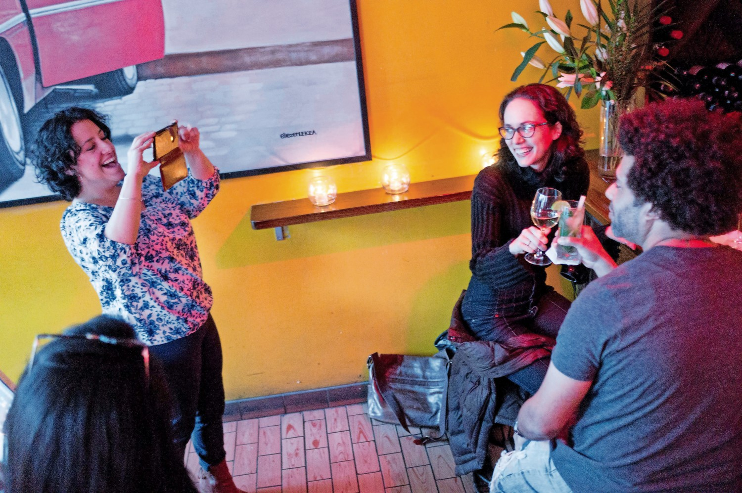 Lehman College professor Teresita Levy, left, takes a picture of graduate students Sophia Cutler and Ivan Waldo at Amor Cubano.