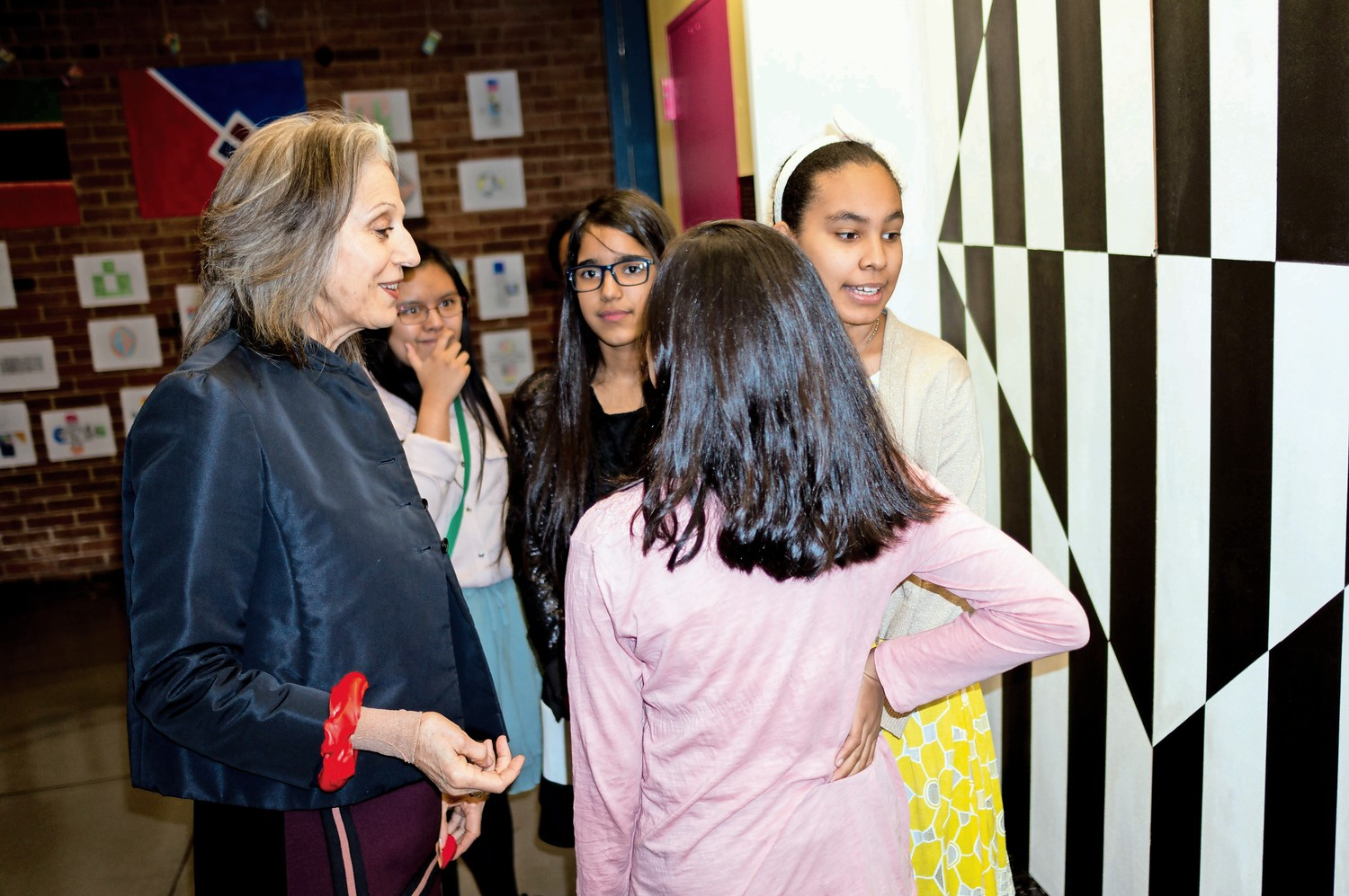 Ruth Lande Shuman, the founder of Publicolor, left, talks to students at M.S. 244 in front of a mural inspired by the work of Carmen Herrera. Publicolor worked closely with students at M.S. 244 to reproduce one of Herrera's paintings.