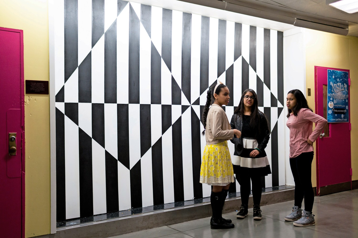M.S. 244 students Mariam Alberto, Sherlyn Munez and Sily Netapongot talk in front of a reproduction of a painting by Carmen Herrera. They worked with other classmates and the organization Publicolor to bring the painting to life.