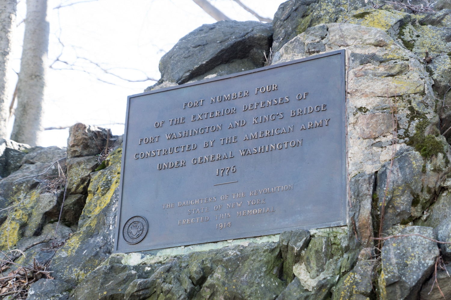 A plaque commemorating Kingsbridge Heights's historical significance is built into the rock along Reservoir Avenue.