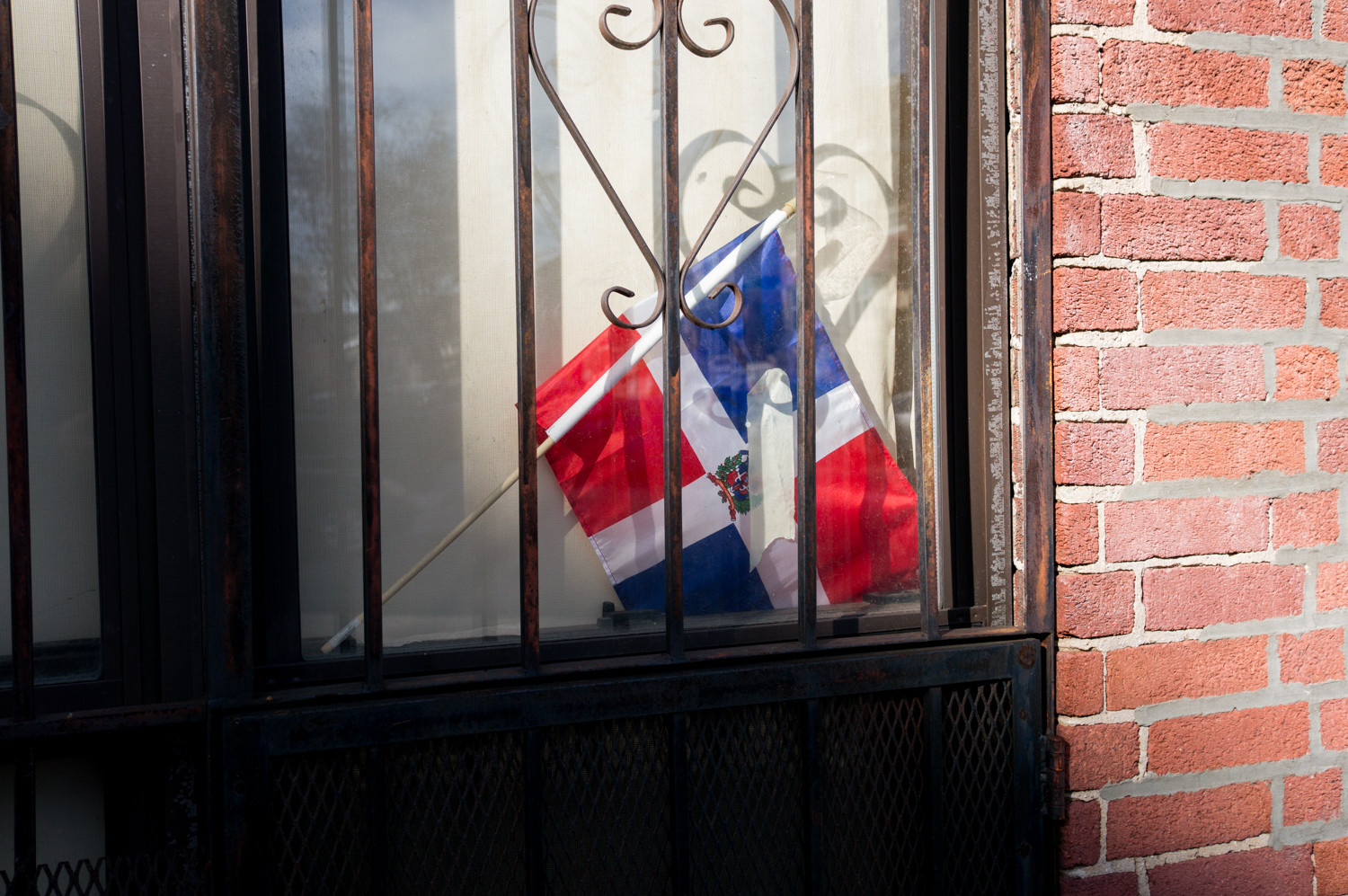 The national flag of the Dominican Republic rests in the window of an apartment in Kingsbridge Heights.