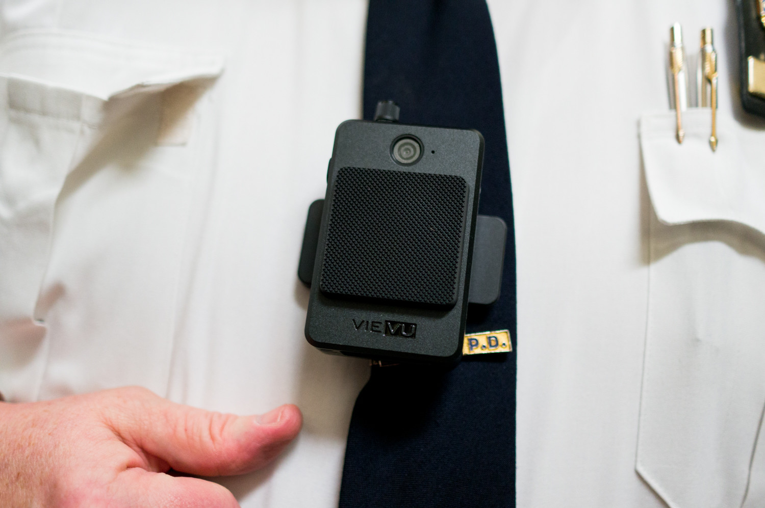 Deputy Inspector Terence O'Toole of the 50th Precinct demonstrates wearing a body camera, which patrol officers under his command began using March 20. Frederick Davie, acting chair of the city's Civilian Complaint Review Board, has stressed the importance of video evidence to the board's investigations.