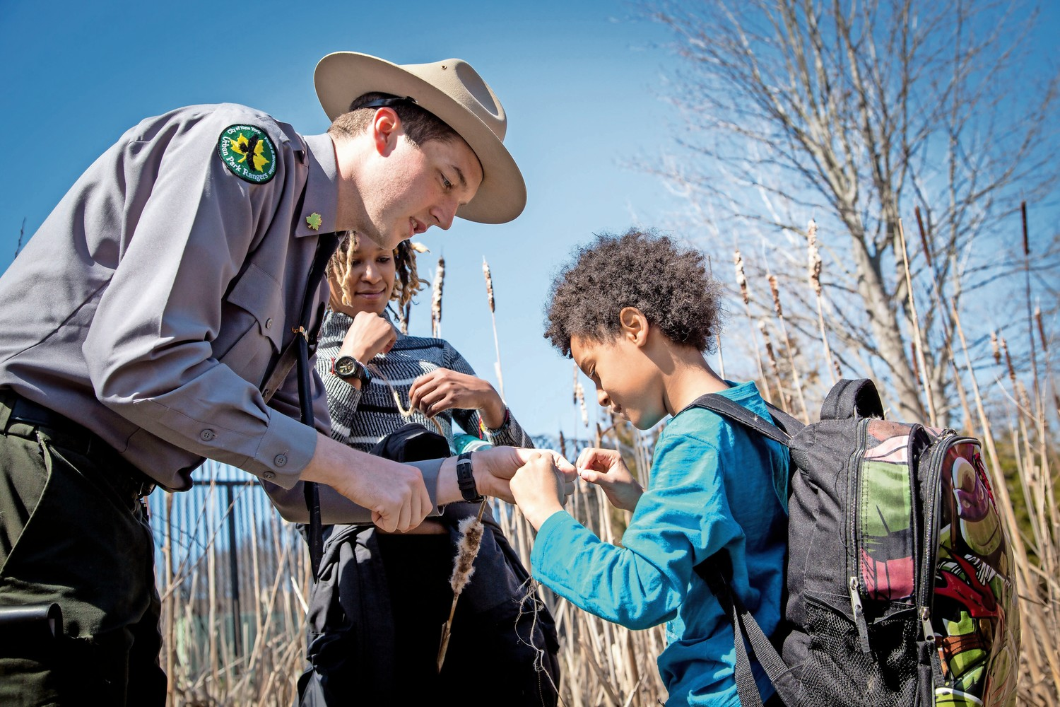 Ian Cleary, an urban park ranger, shows Ajani Parker the parts of a cattail plant in the ?Survival Series? workshop in Van Cortlandt Park.