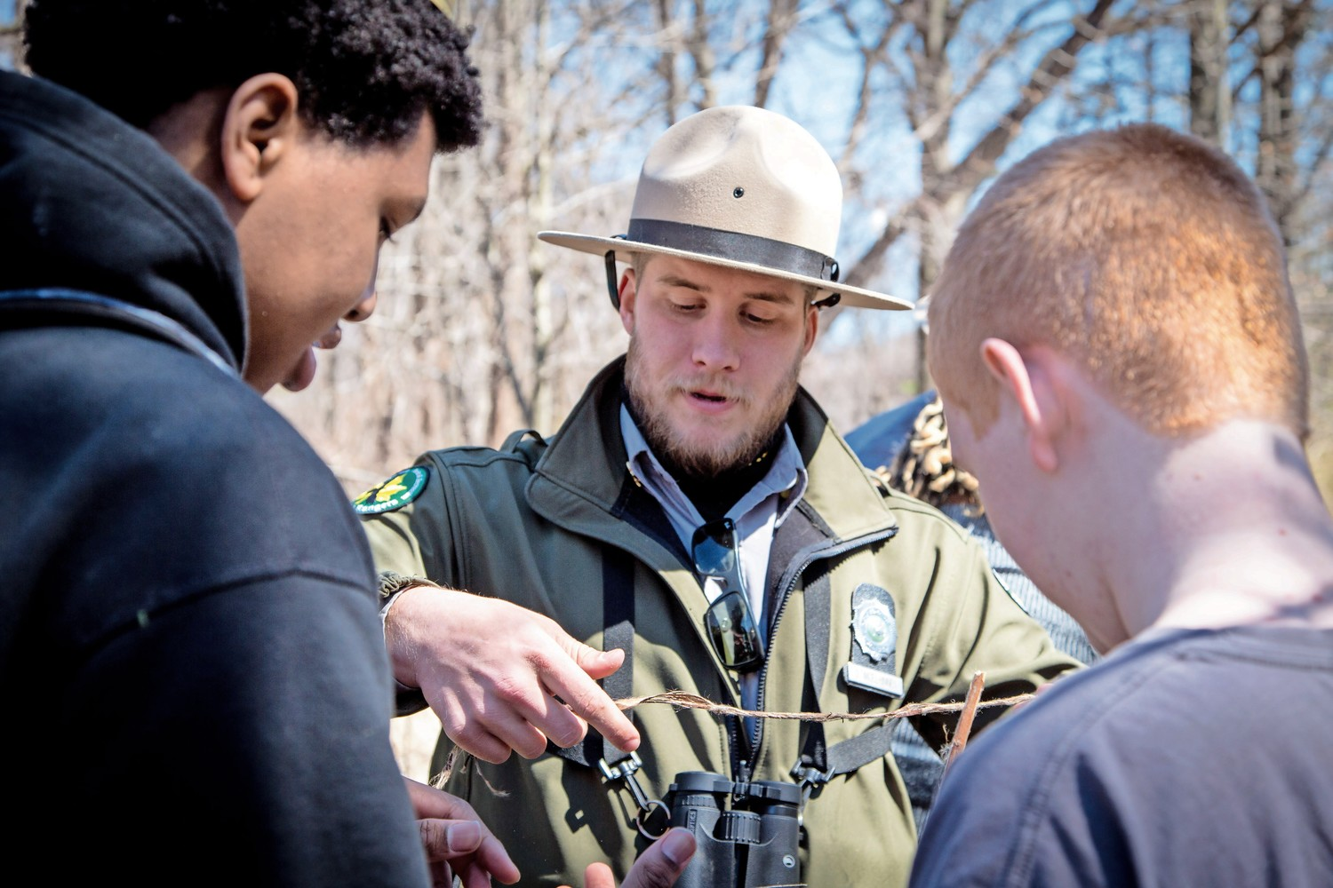 Dan McElhinney, an urban park ranger, shows two teenage boys how to make cordage out of dogbane in the ?Survival Series? workshop in Van Cortlandt Park.