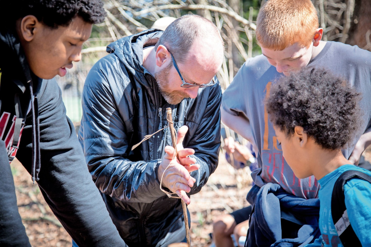 John Doran shows his son, Aidan, and two boys how to make use of natural supplies at the 'Survival Series' workshop in Van Cortlandt Park.