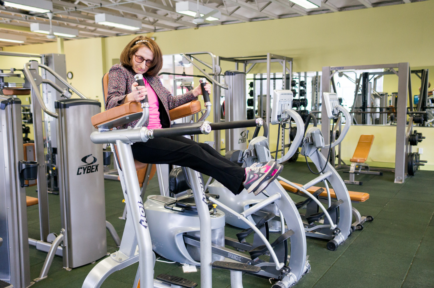 Judy Fettman does leg raises in the health club at the Skyview-on-the-Hudson co-op in North Riverdale. Fettman lives with familial dysautonomia, a genetic condition that affects the development and survival of certain nerve cells and occurs primarily in people of Ashkenazi Jewish descent.