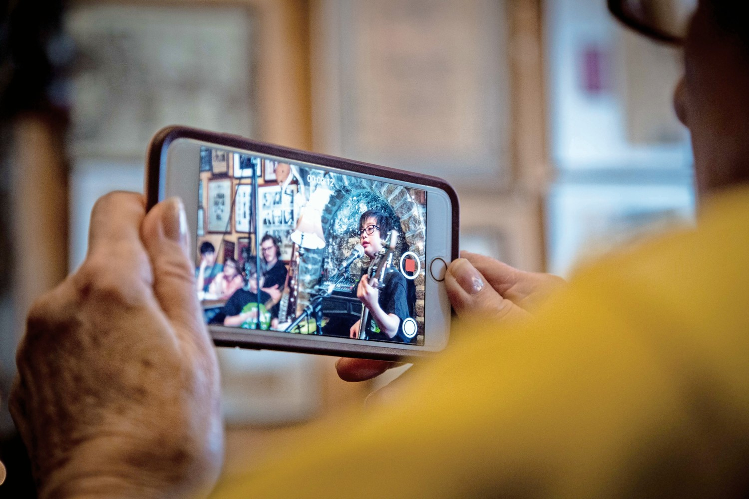 A fan of The Great Oaks takes a video of the band playing their set at An Beal Bocht Cafe.