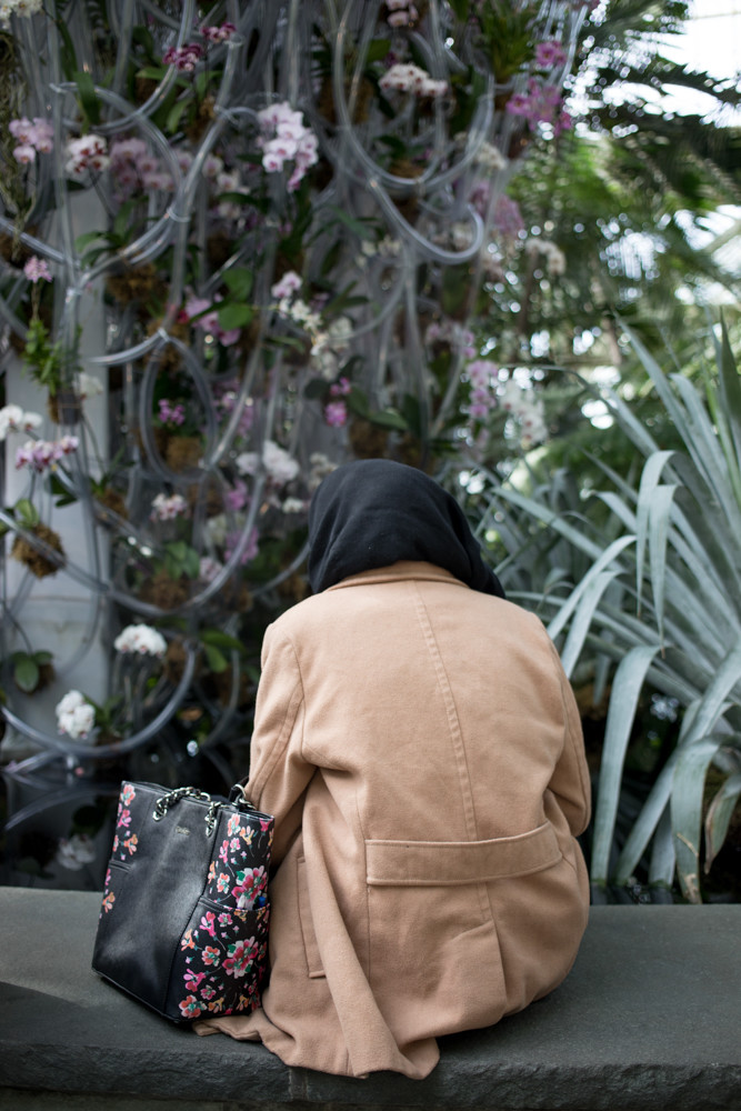 A visitor to the New York Botanical Garden's orchid show rests next to one of Daniel Ost's large installations.