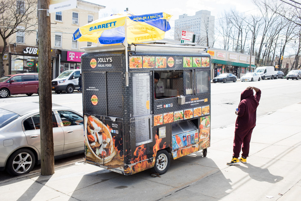 A customer waits for his order at Jolly's Halal Food cart on Riverdale Avenue. Islam Moseama, who operates the cart, says he was looking for a neighborhood less saturated with food trucks to set up shop. Previously, his cart served food to hungry Hunter College students on Manhattan's Upper East Side, where 10 or 15 competitors jostled for business.