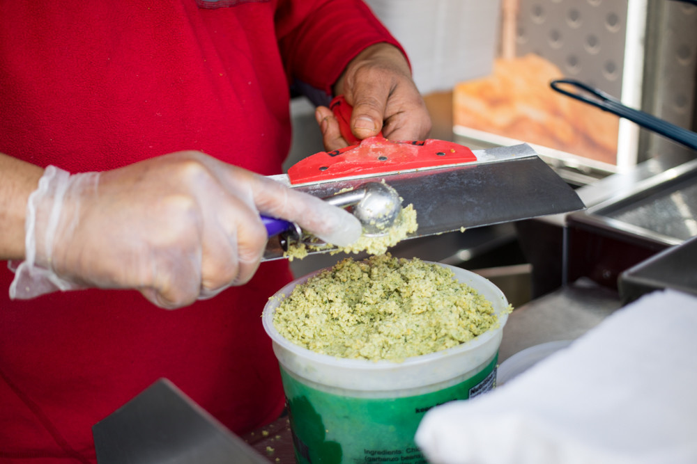 Mohammed Awed scoops ground chickpeas for falafel with fluffy pita, which he sells along with lamb, chicken, fish and shrimp over rice, out of Jolly's Halal Food cart, which made its Riverdale Avenue debut April 4 for a few days before disappearing that Friday.