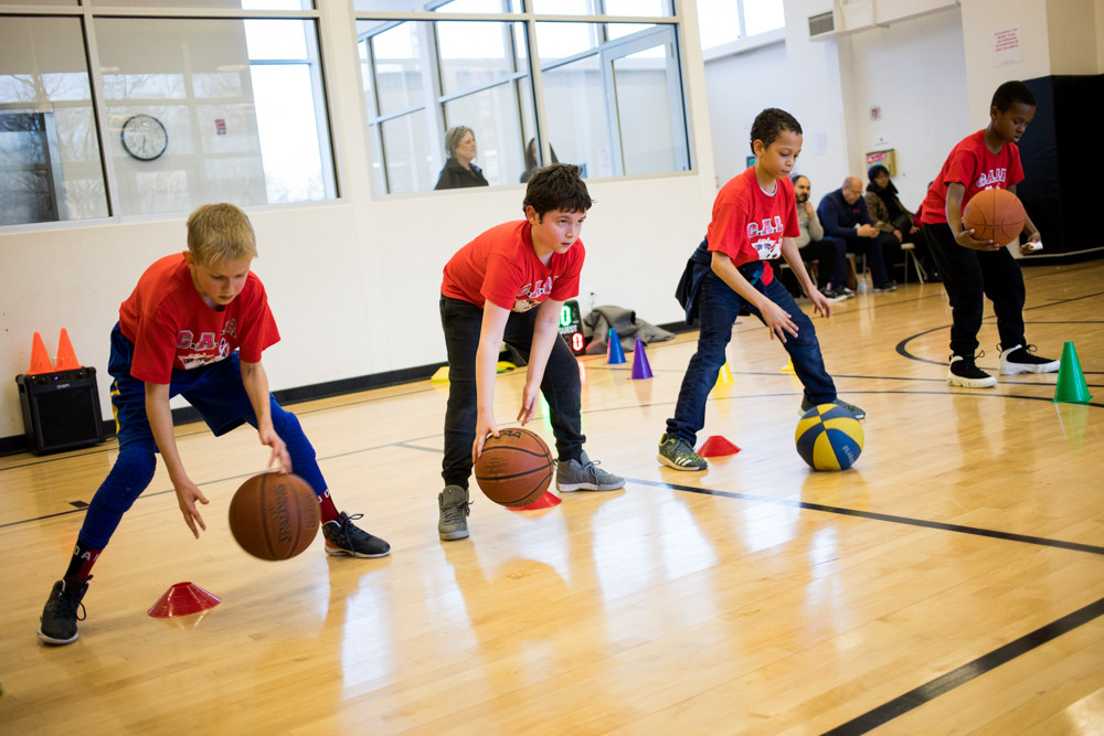 Members of the after-school basketball program Courageous Athletic Leaders Forever practice dribbling in the gym at Riverdale Neighborhood House.