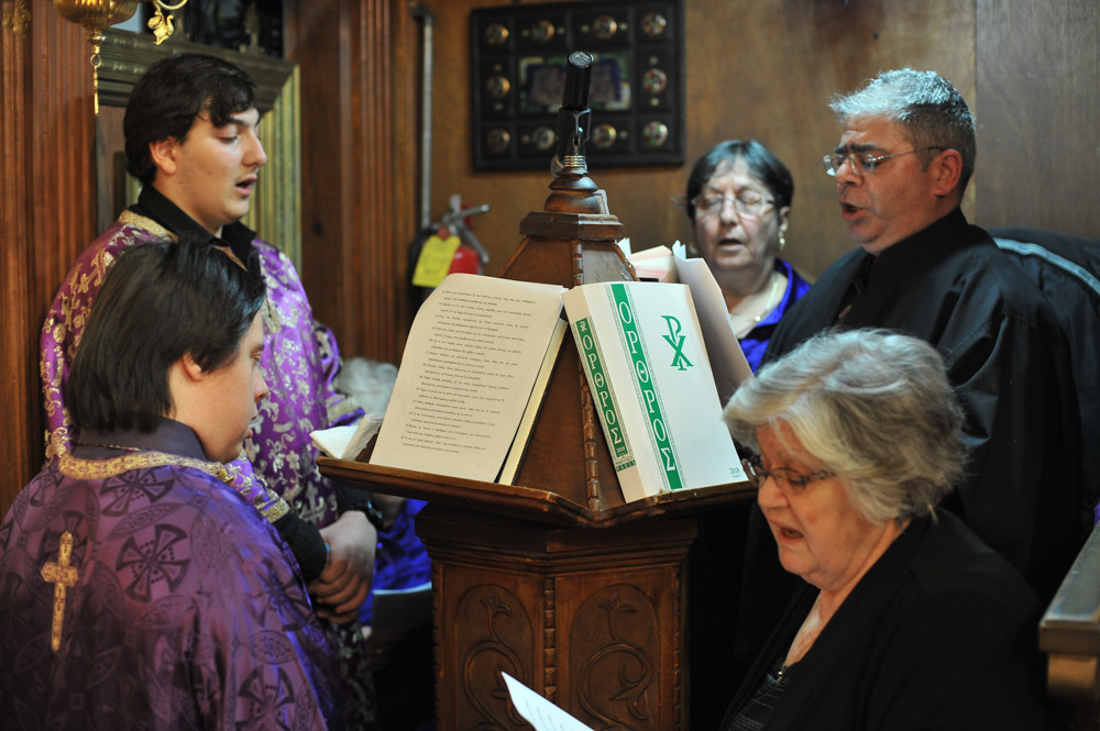 Chanters in the Greek Orthodox Church of St. Nektarios chant prayers during the evening service on Good Friday.