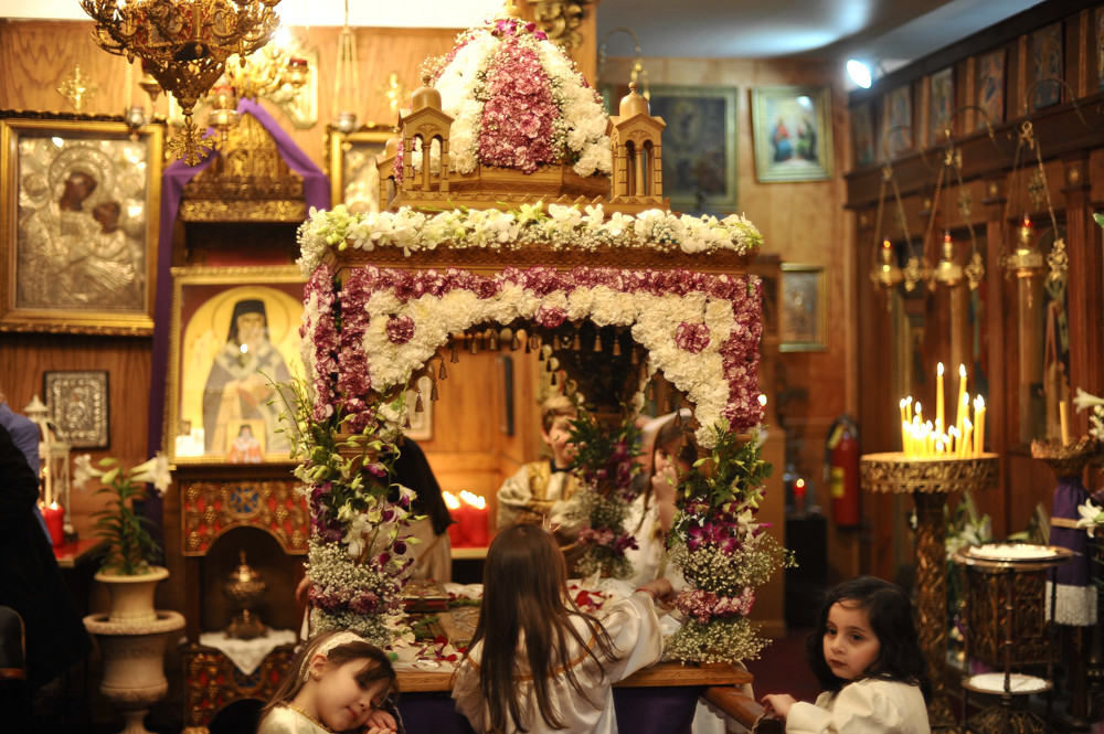 Young girls dressed as myrophores surround the epitaphio, an ornate representation of Jesus Christ's tomb, in the Greek Orthodox Church of St. Nektarios. In the Greek Orthodox tradition, myrophores symbolically represent the myrrh-bearers who were involved in the burial of Jesus Christ.