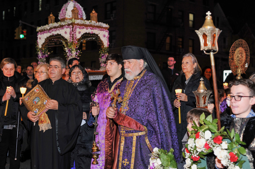 Clergy and congregants in the Greek Orthodox Church of St. Nektarios walk outside with the epitaphio, an ornate representation of Jesus Christ's tomb, during the evening service on Good Friday. The procession is meant to represent the funeral procession of Jesus Christ.