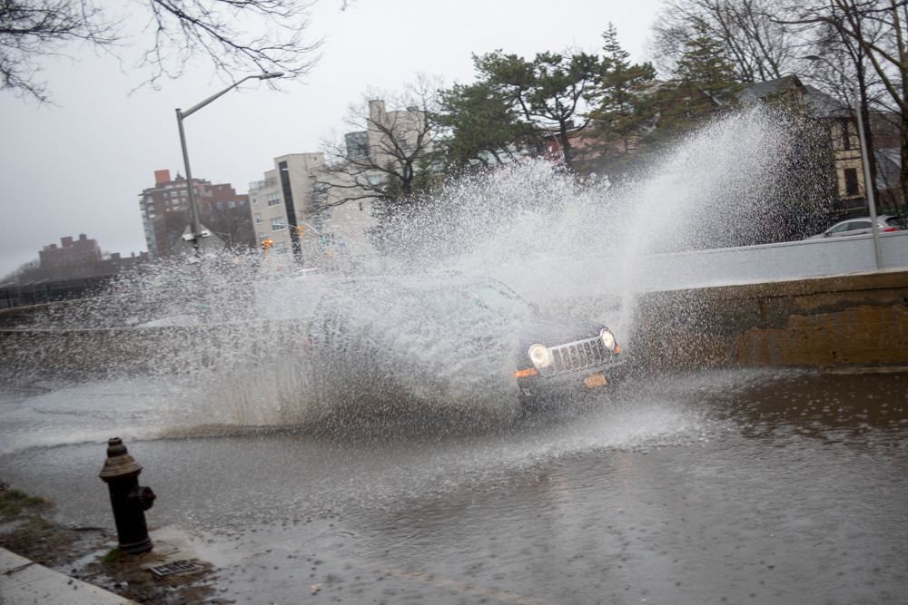 A car plows through a flooded section of Henry Hudson Parkway West during a storm.
