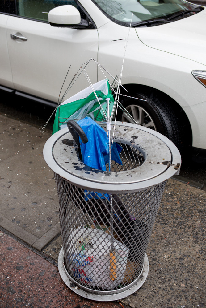 Mangled umbrellas rest in a garbage can during a storm on West 231st Street.