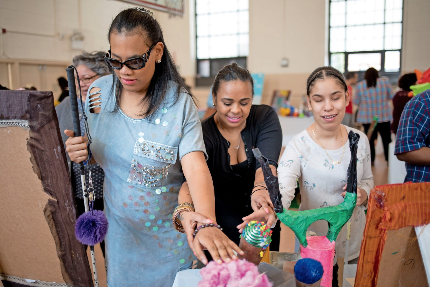 Ashley Moriseau, left, and Ashley Perez, right, feel art with the help of Mari Gonzalez. Moriseau and Perez are students at Lavelle School for the Blind, and both produced works of art for the school's third annual art exhibit.