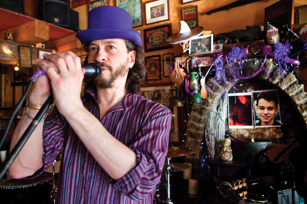 Jeremy Bar-Illan, founder of the Purple Hat Foundation, addresses the audience at An Beal Bocht Café during a fundraiser in 2013 as the portrait of his son Zachary Bar-Illan, who died at the age of 17 from osteosarcoma, hangs visibly as a reminder of the cause.