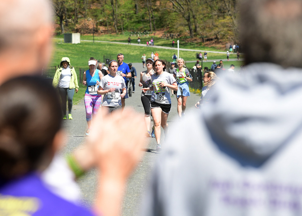Spectators cheer as participants run during Mosaic Mental Health's Healthy Minds, Healthy Bodies 5K last year. The run is part of the organization's annual mission to raise money for its services while increasing awareness about mental health.