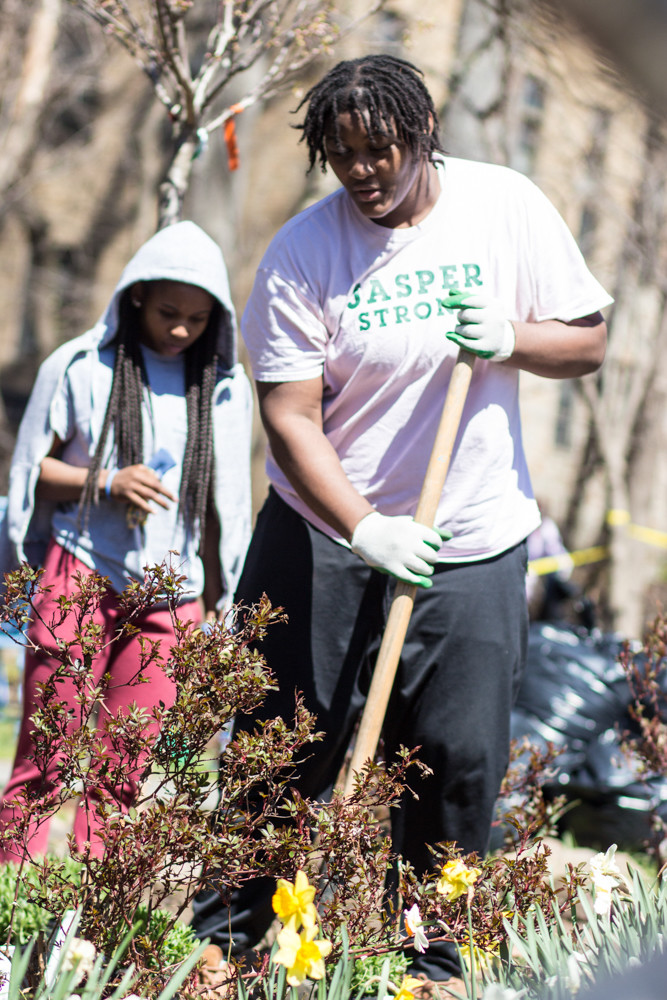 Gabby Cajou, left, and Alex Smith, both members of Manhattan College's women's basketball team, were among those volunteering with the Stewards of Lower Brust Park. Last weekend, the group teamed up with Manhattan College's Green Club to plant flowers in the park's renovated garden.
