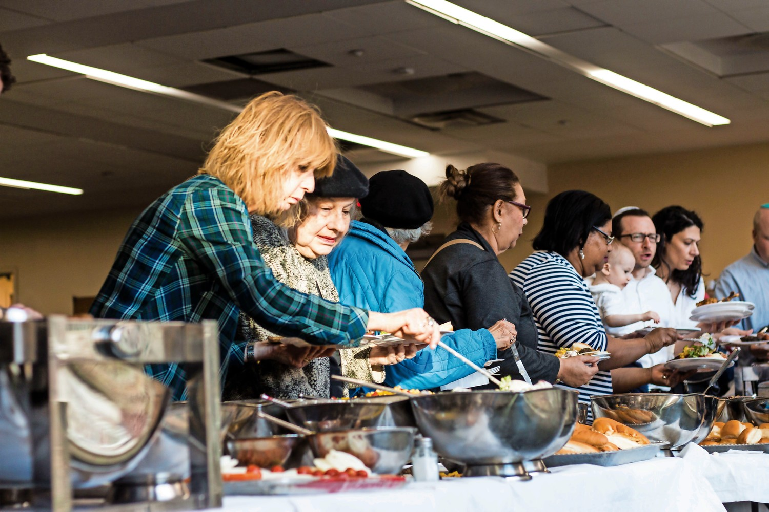 Attendees serve themselves food during the Bronx Israeli Independence Day Festival at the Hebrew Institute of Riverdale. As part of the event's program, free kosher barbeque was provided.