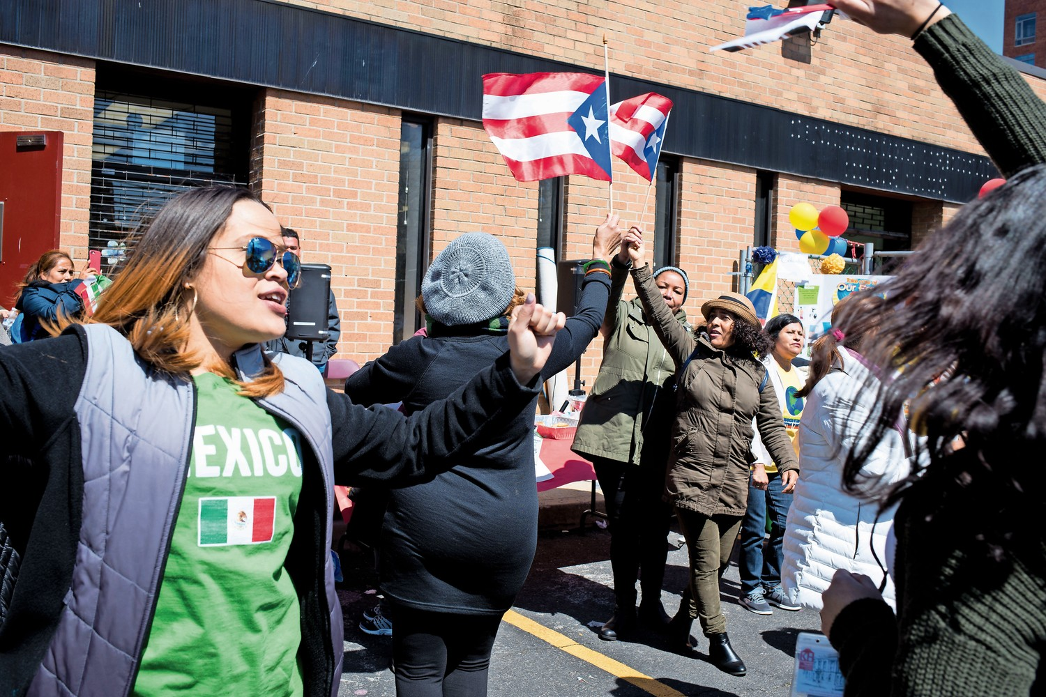 People wave Puerto Rican flags and dance at an Earth Day celebration at the Kingsbridge Heights Community Center's location on West 231st Street.