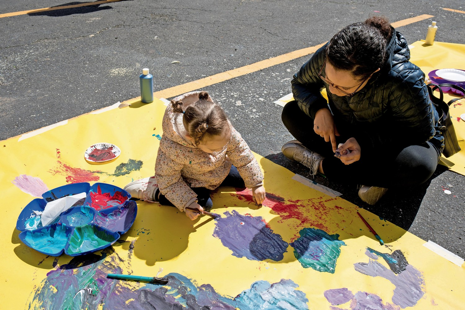 At an Earth Day celebration in Kingsbridge, Lilly Quero paints while her mother, Ilyana Sori, watches.