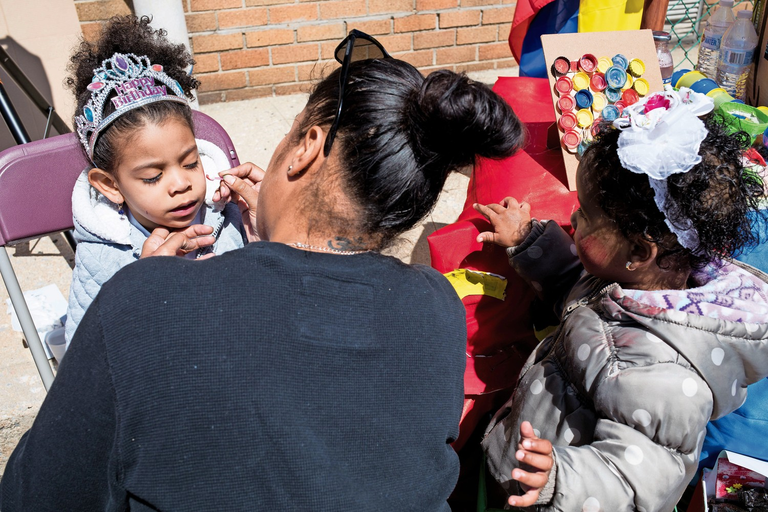 Deborah Ortiz paints Lina Mateo's face while Lina's friend Sherlyn Garcia watches at an Earth Day celebration at the Kingsbridge Heights Community Center's location on West 231st Street.