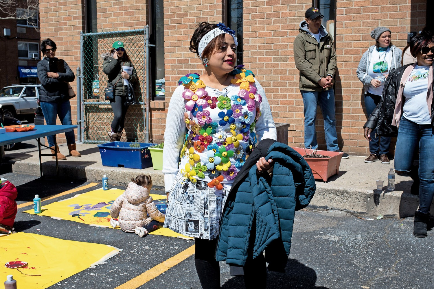 Ana Antigua wears a shirt she decorated with plastic bottles she fashioned into flowers at an Earth Day celebration.