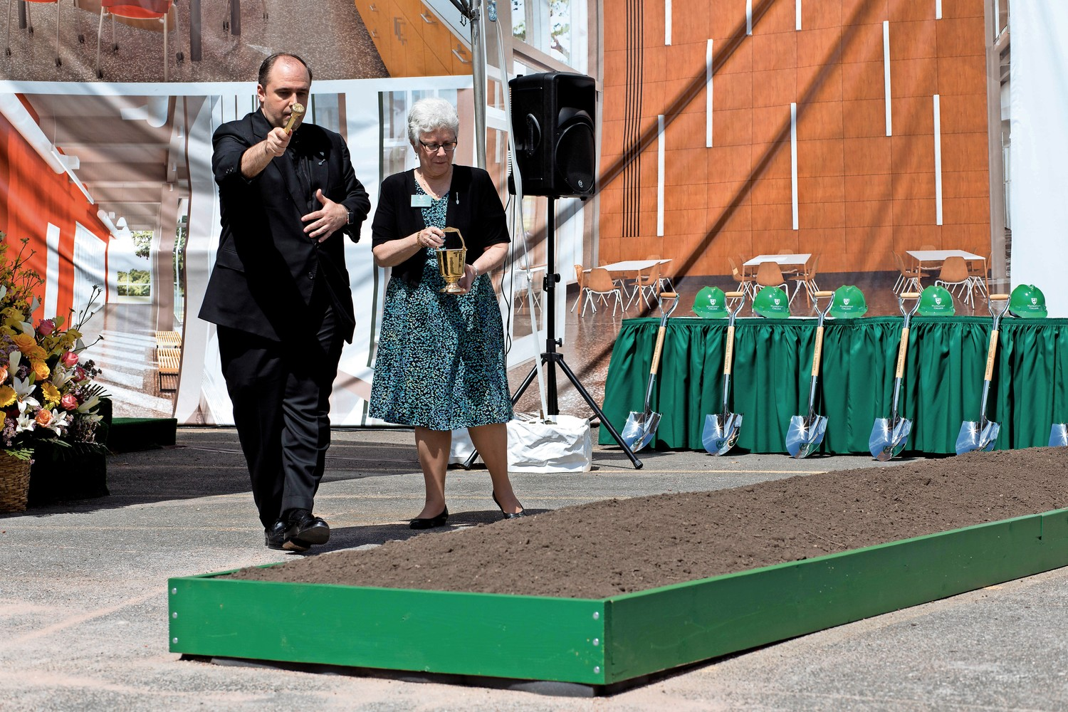 Rev. Thomas Frank, Manhattan College's chaplain, blesses ceremonial soil along with Lois Harr, the assistant vice principal for student life, at a groundbreaking ceremony for the Patricia and Cornelius J. Higgins '62 Engineering and Science Center. The new center is expected to be completed in 2020.