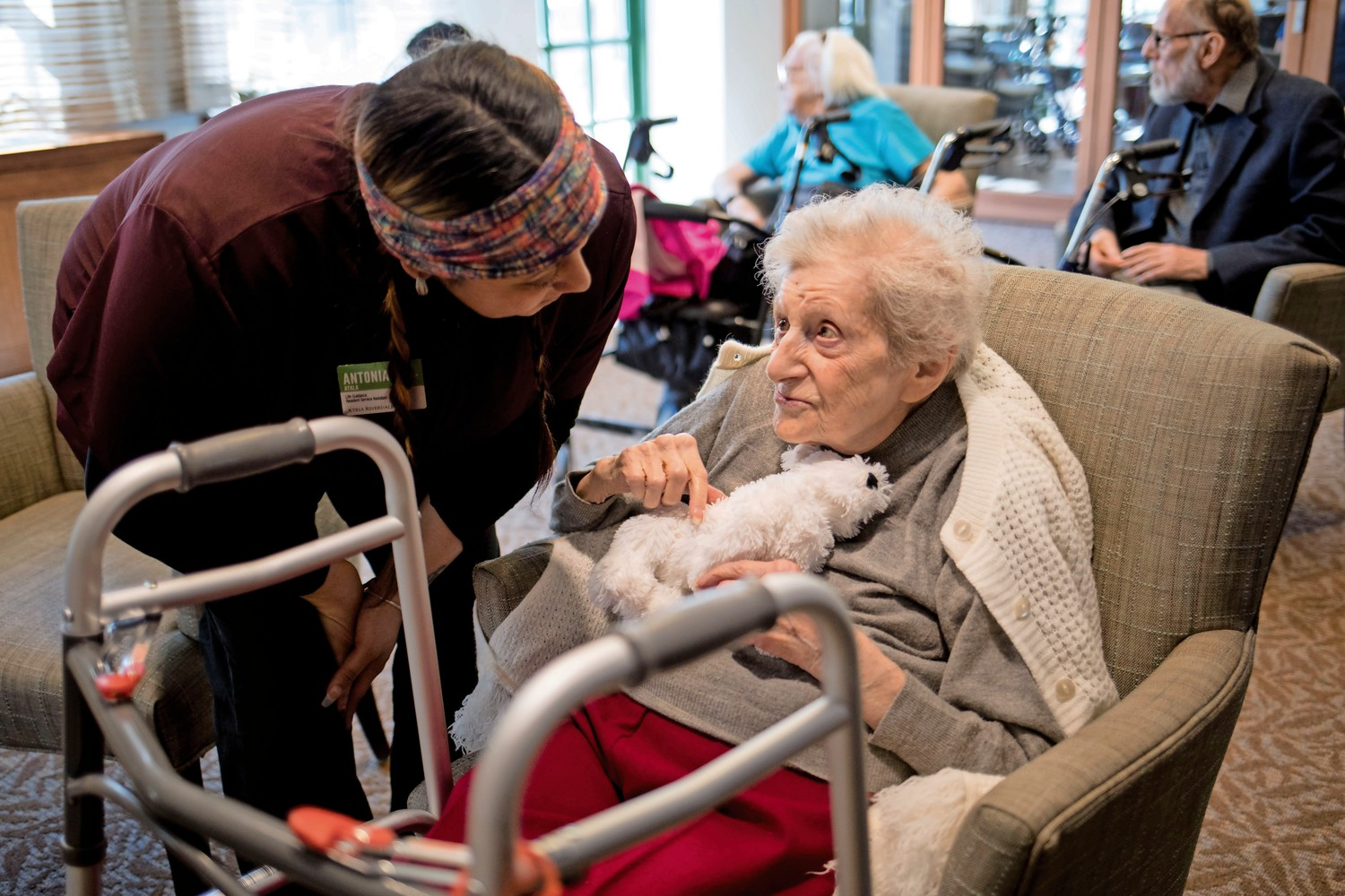Florence Zimmerman, a 103-year-old former judge, holds her stuffed animal, Poopskie, as she hears about the plan for lunch from her caregiver, Antonia Ayala, at Atria Riverdale.