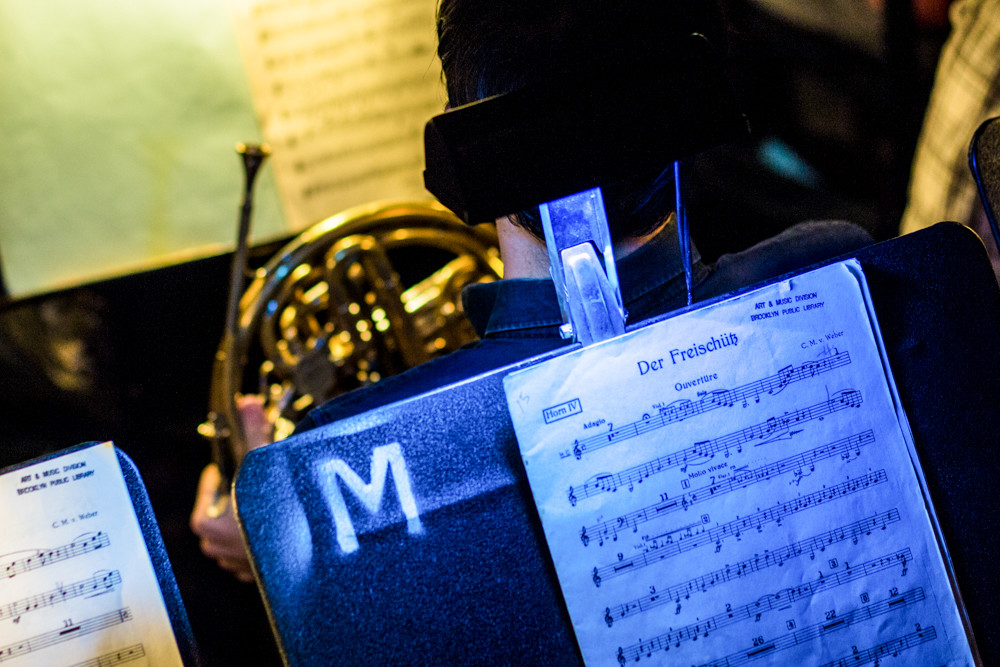 A dim, blue light illuminates the sheet music for Carl Maria von Weber's 1821 opera 'Der Freischütz.' The Bronx Opera Company will perform an English language version of the production at Lehman College's Lovinger Theater this weekend.