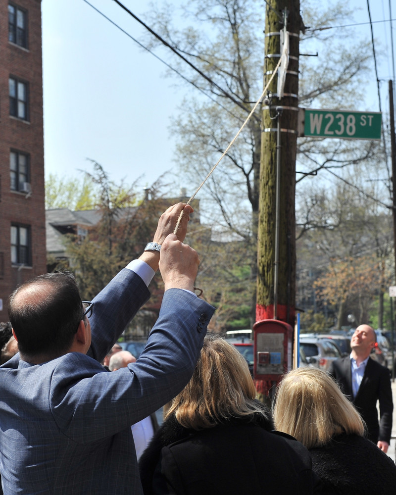 Councilman Andrew Cohen pulls the wrapping off a new street sign at the intersection of West 238th Street and Waldo Avenue. The avenue has been ceremoniously co-named 'Andrew Sandler Way' to honor the former Community Board 7 district manager who died last year.