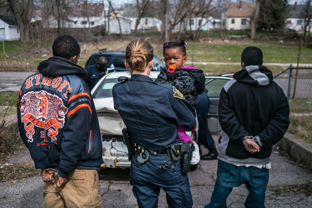 Officer Bridget Balasko holds a small child while her father is being searched and questioned in March 2016. It is part of 'Flint is a Place' at the Bronx Documentary Center.