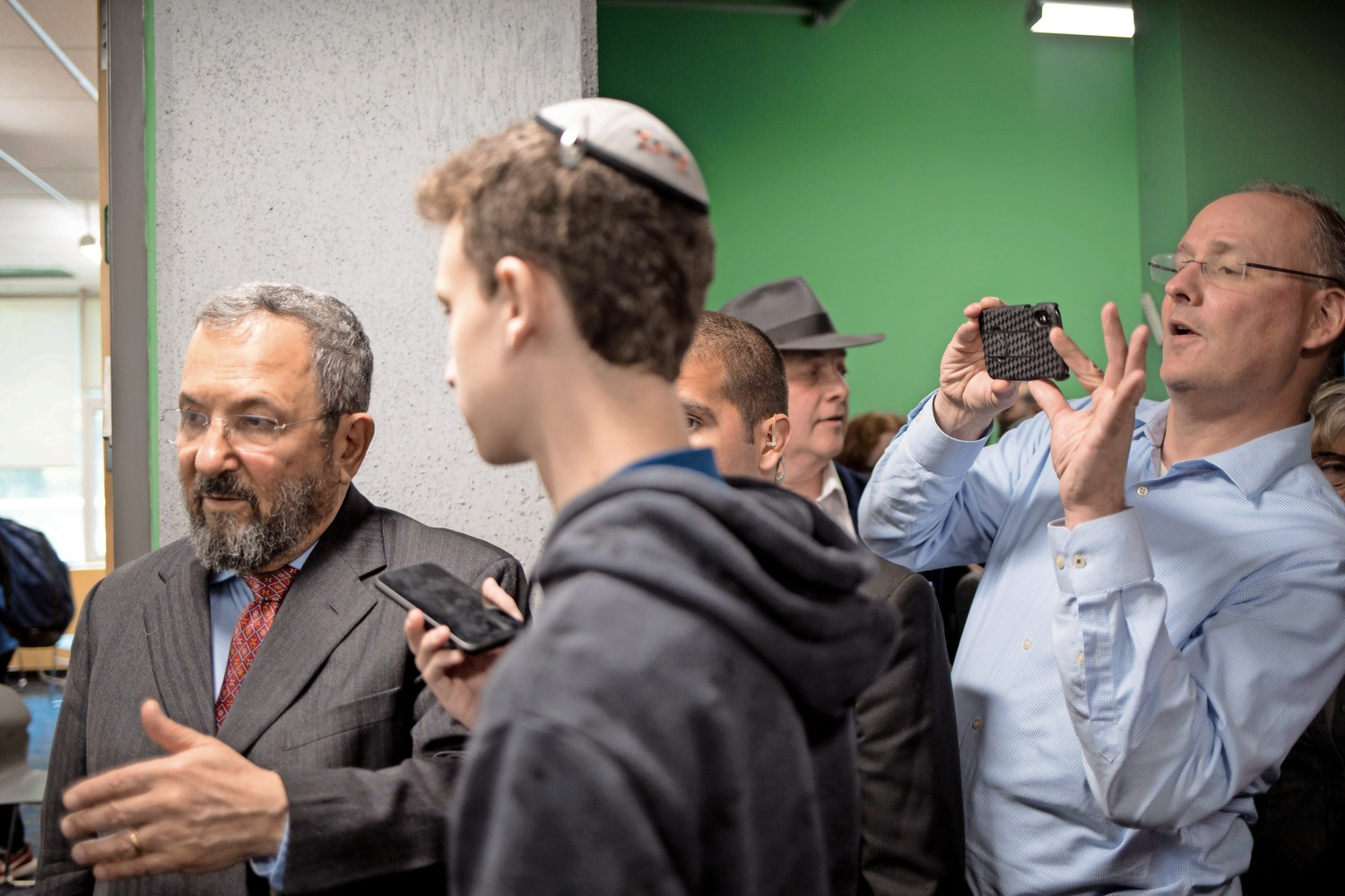 Former Israeli prime minister Ehud Barak, left, speaks with students in the hallway at SAR High School. Barak's visit to the school in honor of Israel's 70th anniversary coincided with the opening of the U.S. embassy in Jerusalem, which saw an outbreak of violence in Gaza where Israeli forces killed at least 50 Palestinians.