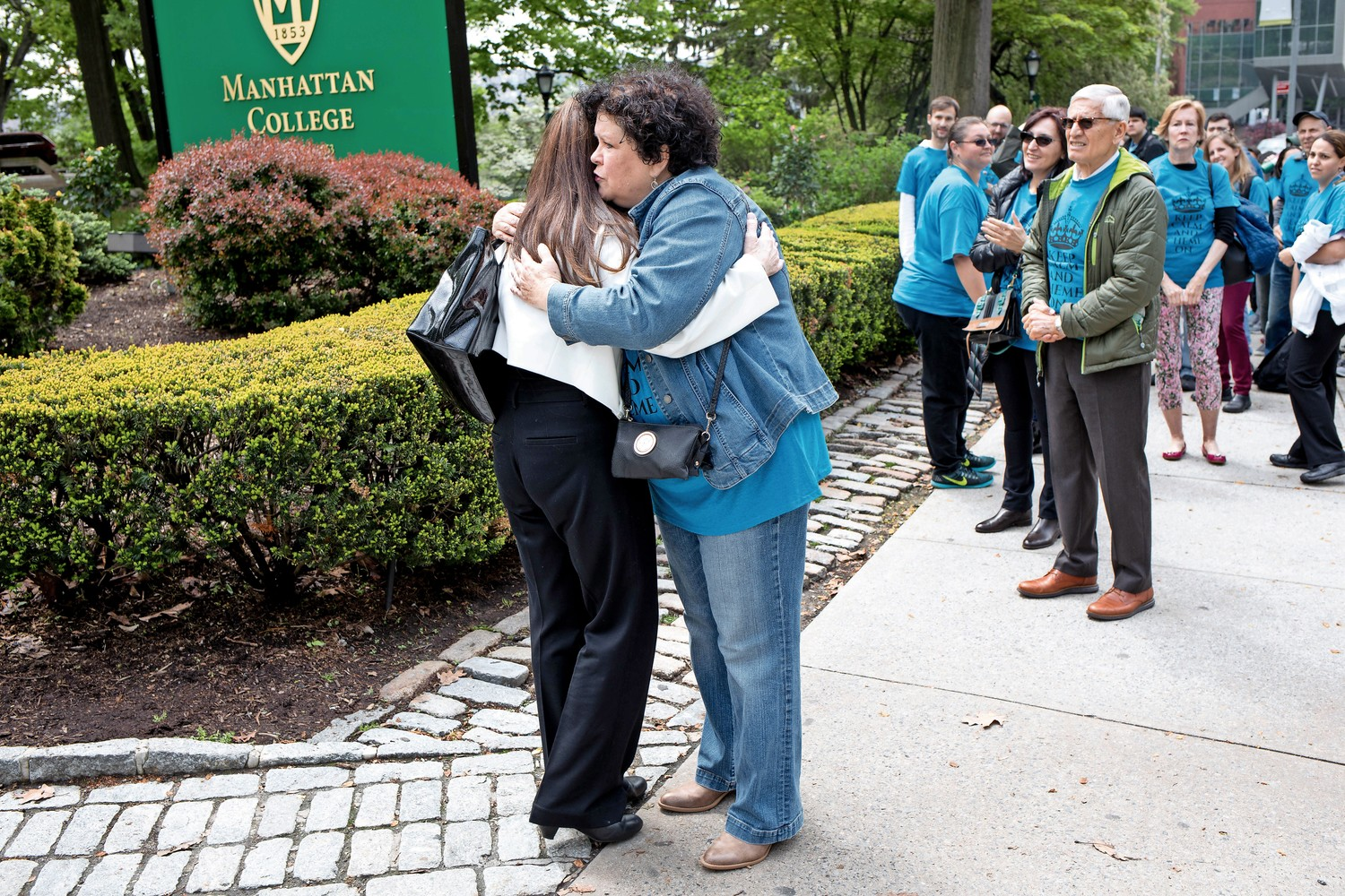 Ann Marie Flynn, left, hugs her sister-in-law, Kerry Brady, outside Manhattan College. A professor of chemical engineering, Flynn attended her preliminary termination hearing.