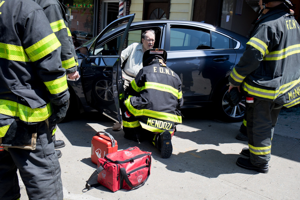 A firefighter helps the 82-year-old driver of a Subaru that crashed into the Kumon Math and Reading Center's North Riverdale location around lunchtime May 9. The man, whose name hadn't been released as of last Monday, reportedly thought he had his foot on the break, but actually had it on the accelerator, police said, reversing his car straight into the storefront.