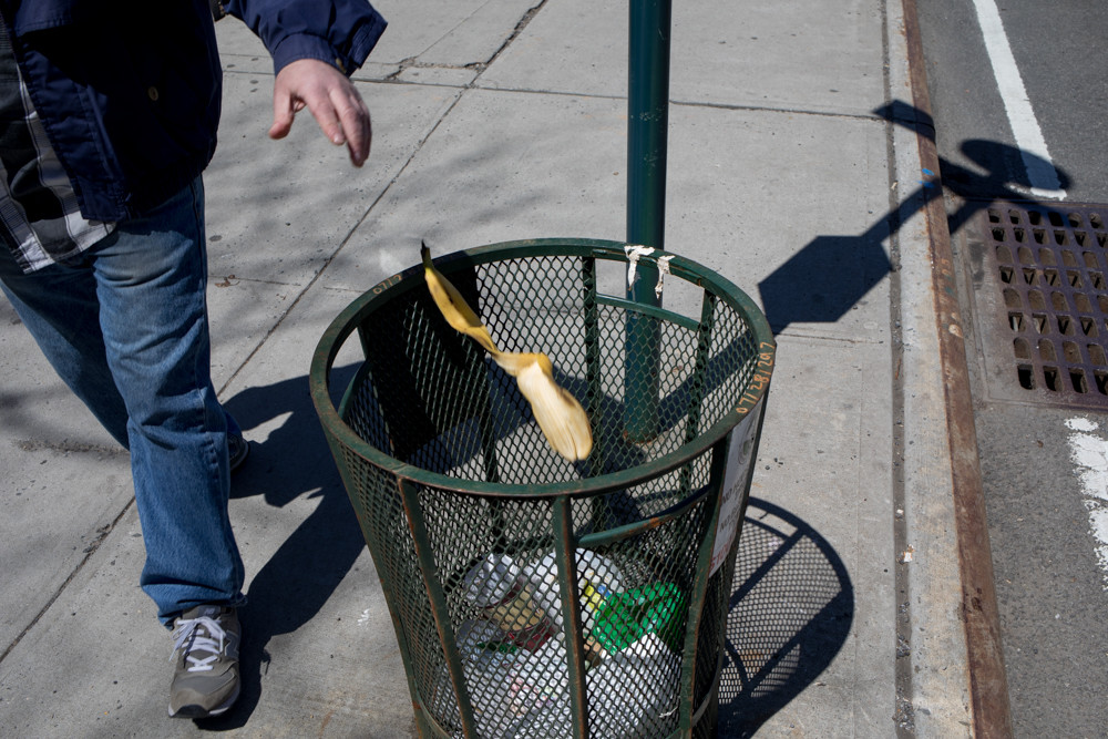A pedestrian tosses a banana peel in a garbage bin near the Riverdale Monument on the corner of West 239th Street and Henry Hudson Parkway East. A number of wire mesh trash baskets have gone missing recently throughout the neighborhood, according to Community Board 8 environment and sanitation committee chair Laura Spalter, much to the chagrin of local residents. The basket near the monument disappeared for a time before reappearing.