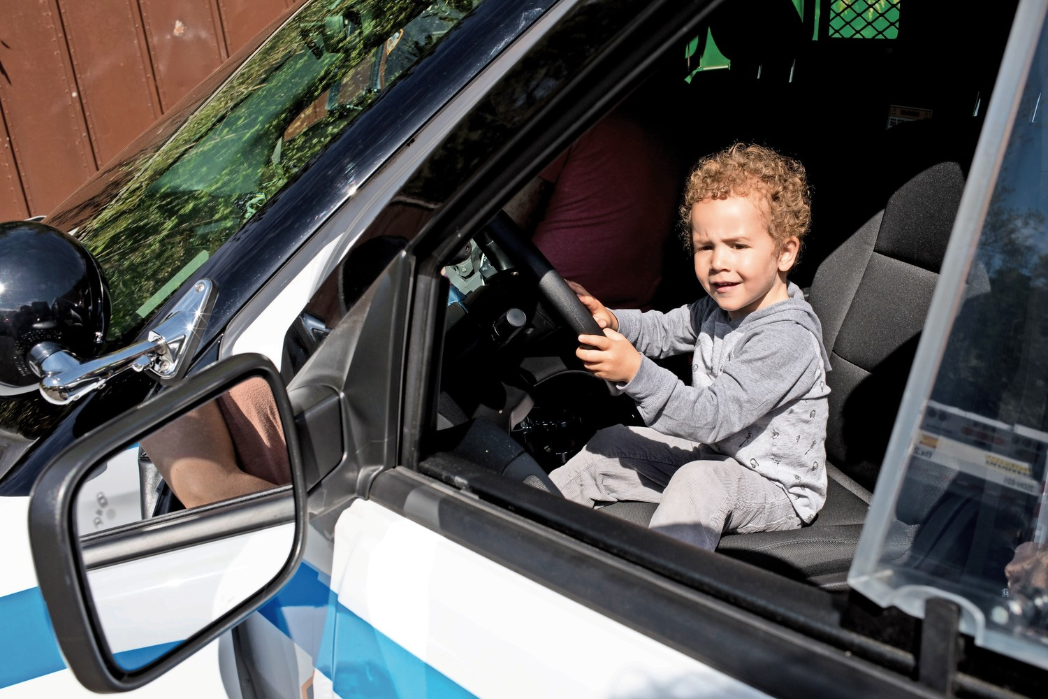 Cole Dunphy honks a police car's horn during Truck Day at the Riverdale Temple. Truck Day brings together vehicles from various municipal agencies, including the police, fire and sanitation departments.