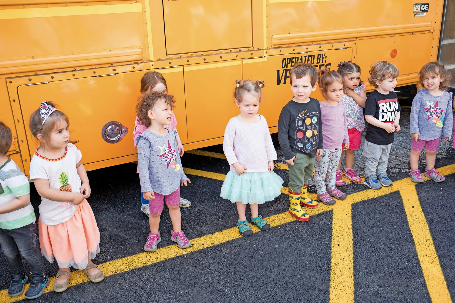 Kids line up outside of a school bus before moving onto the next vehicle during Truck Day at the Riverdale Temple.