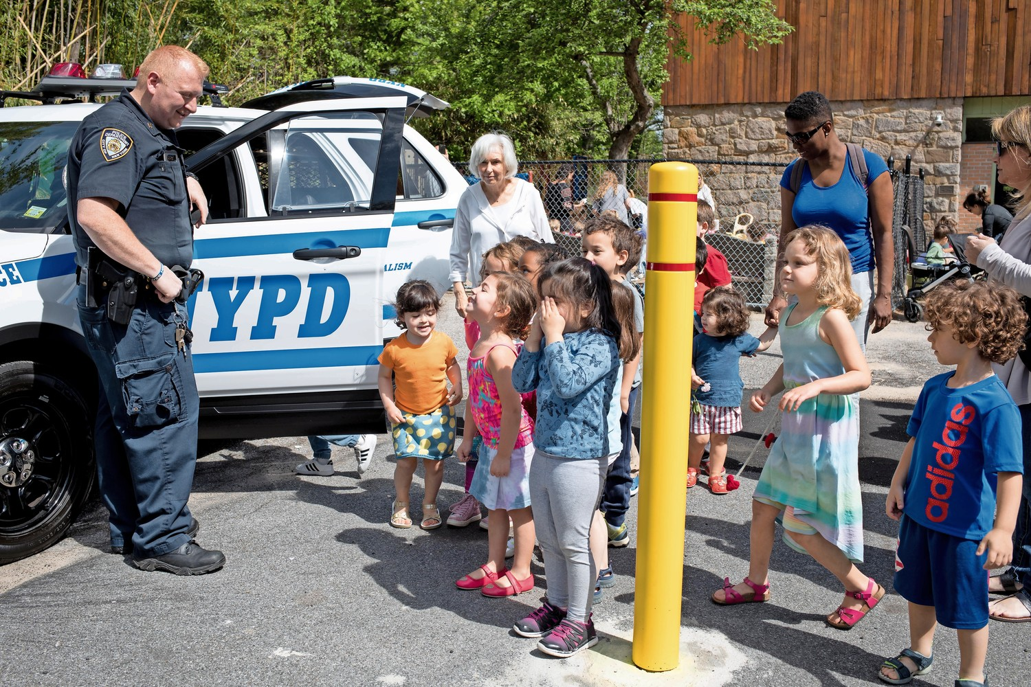 Neighborhood coordination officer Robert Edsall talks with kids outside of his police car during Truck Day at the Riverdale Temple.