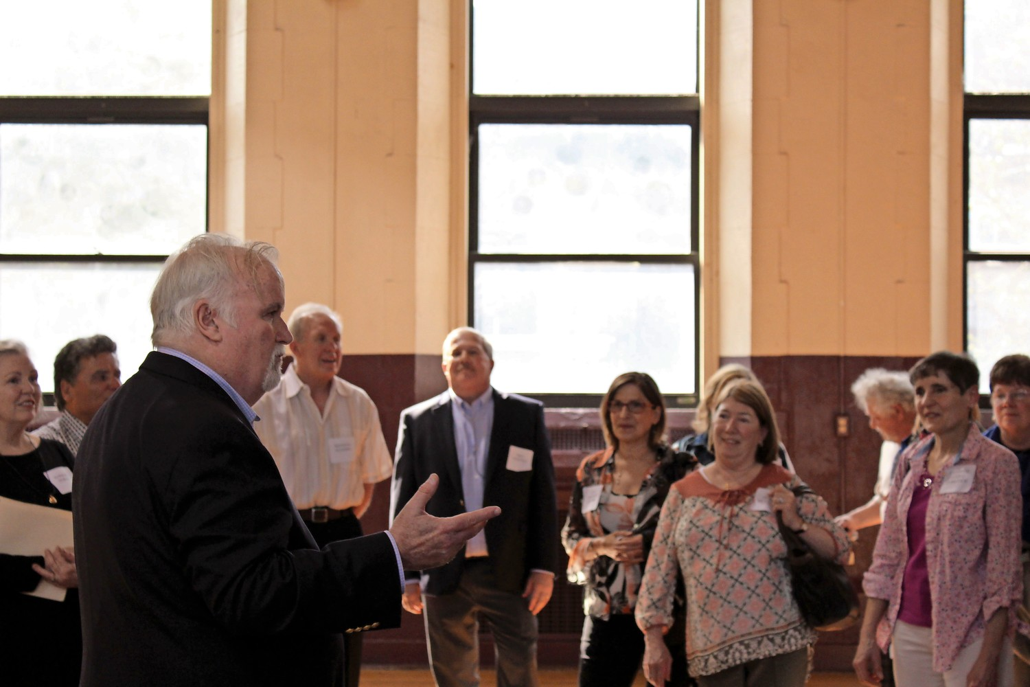 Joe Gunn, one of the organizers of the 50-year reunion, talks to attendees prior to the start of a tour of the St. Margaret of Cortona School.