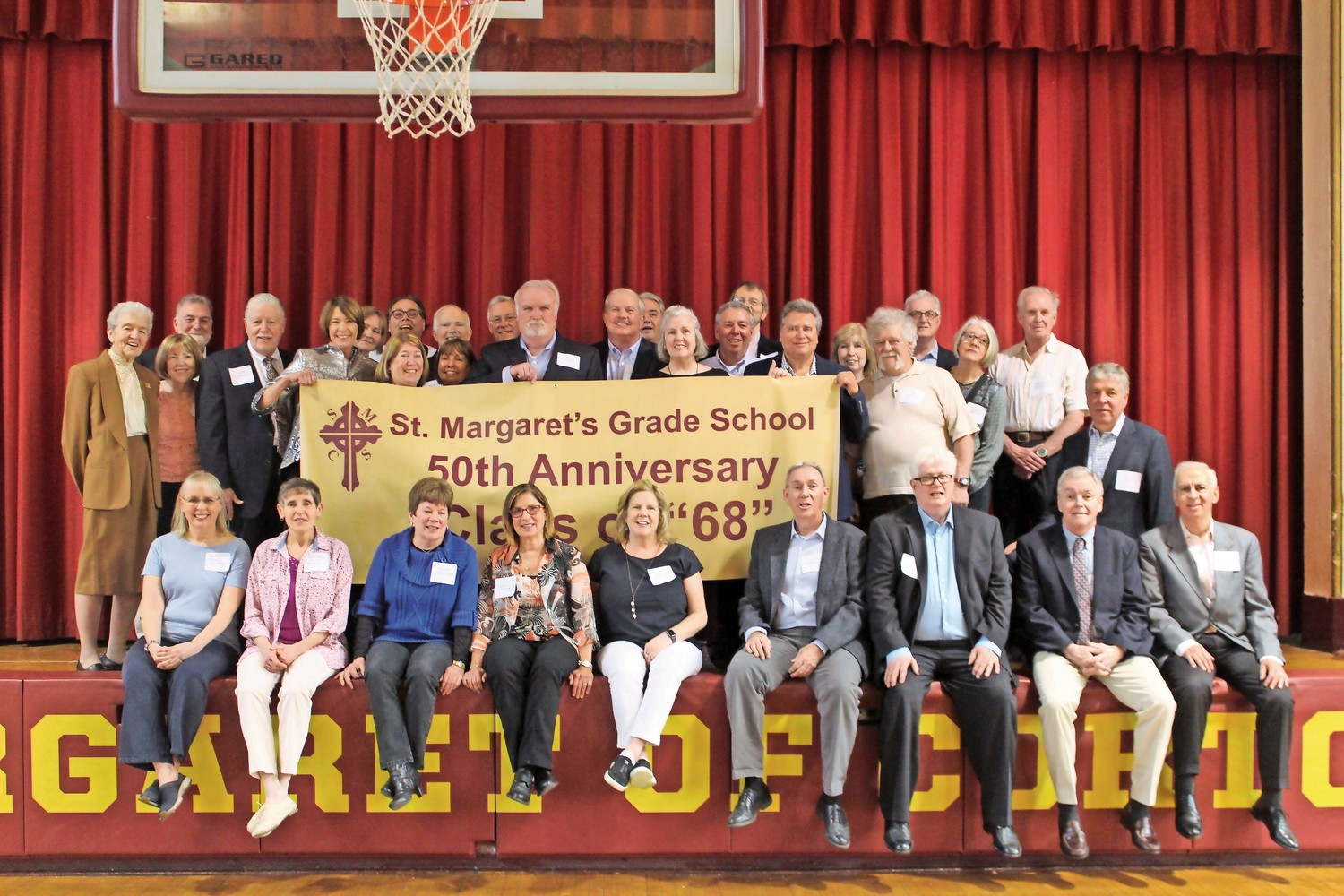 Members of the Class of 1968 gather onstage at the end of their 50th anniversary reunion at St. Margaret of Cortona School.